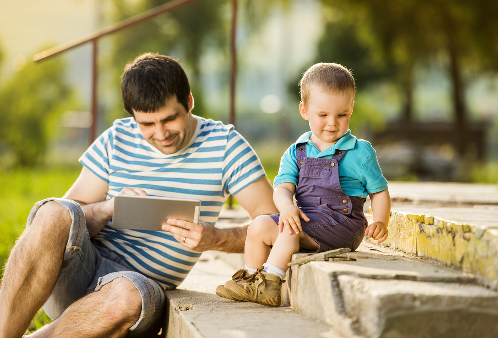 Father and son playing on digital tablet outside