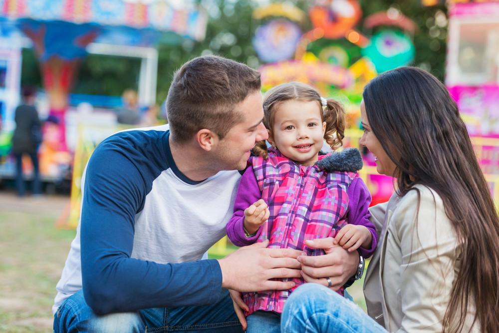 Father, mother and daughter having fun in amusement park, fun fair