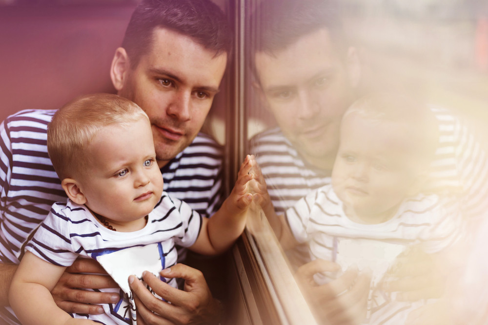 Father with son travel in retro train. They are looking out of window.
