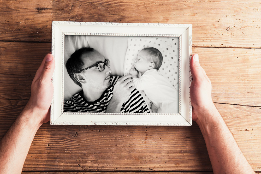 Fathers day composition. Hands of unrecognizable man holding black-and-white photo in picture frame. Studio shot on wooden background.