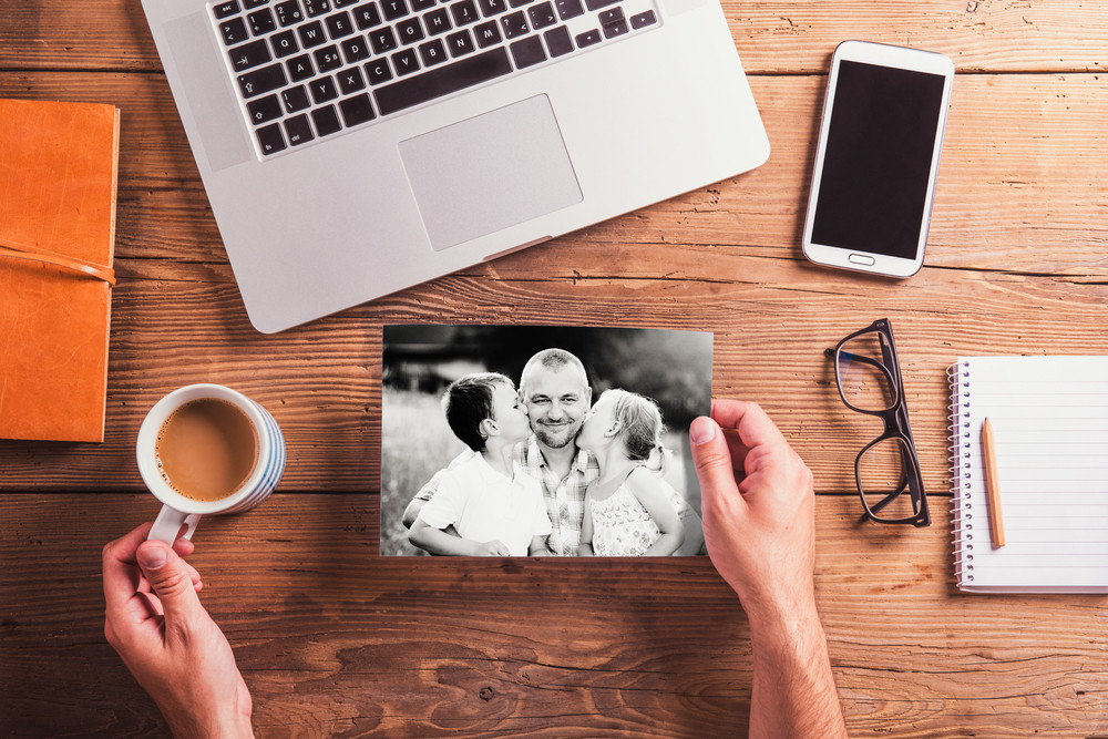 Fathers day composition. Hands of unrecognizable man holding black-and-white photos. Office desk. Studio shot on wooden background.