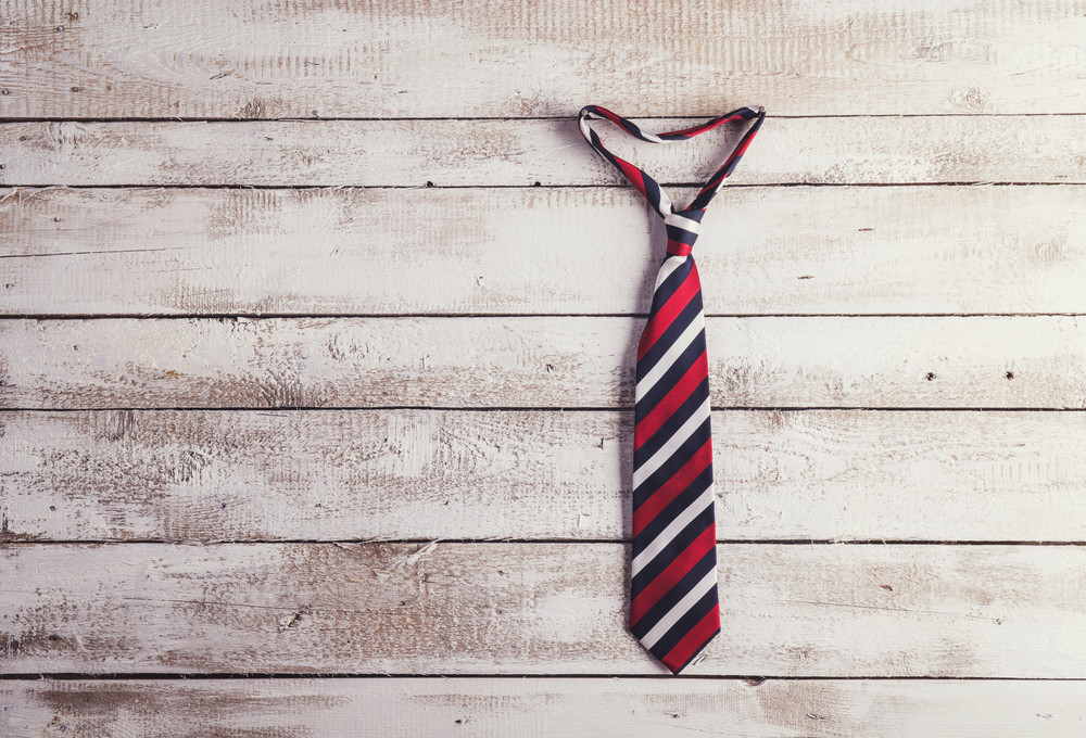 Fathers day composition of colorful tie hang on wooden wall background.