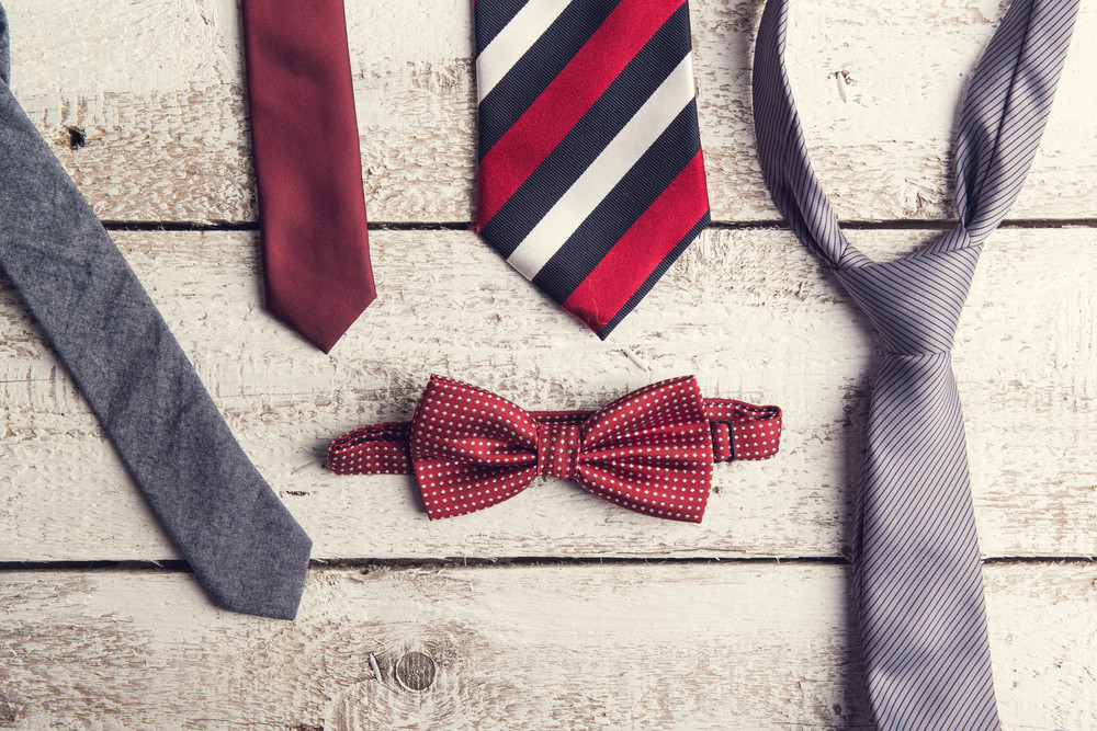 Fathers day composition of colorful ties and bow tie laid on wooden floor backround.
