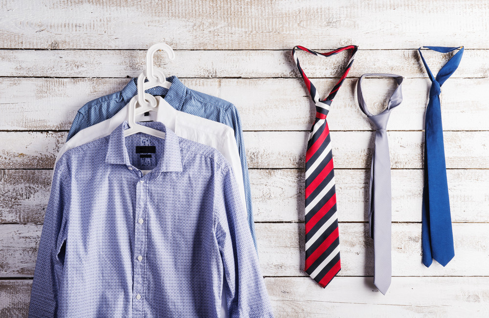 Fathers day composition of shirts and ties hang on wooden wall background.