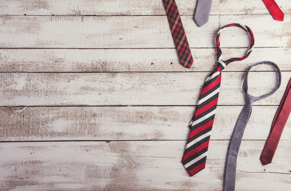 Fathers day composition of various colorful ties laid on wooden floor background.