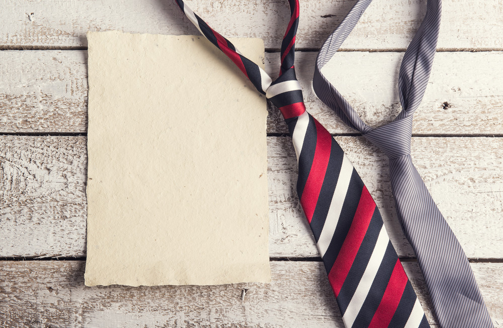 Fathers day composition - ties and empty sheet of paper. Studio shot on wooden background.