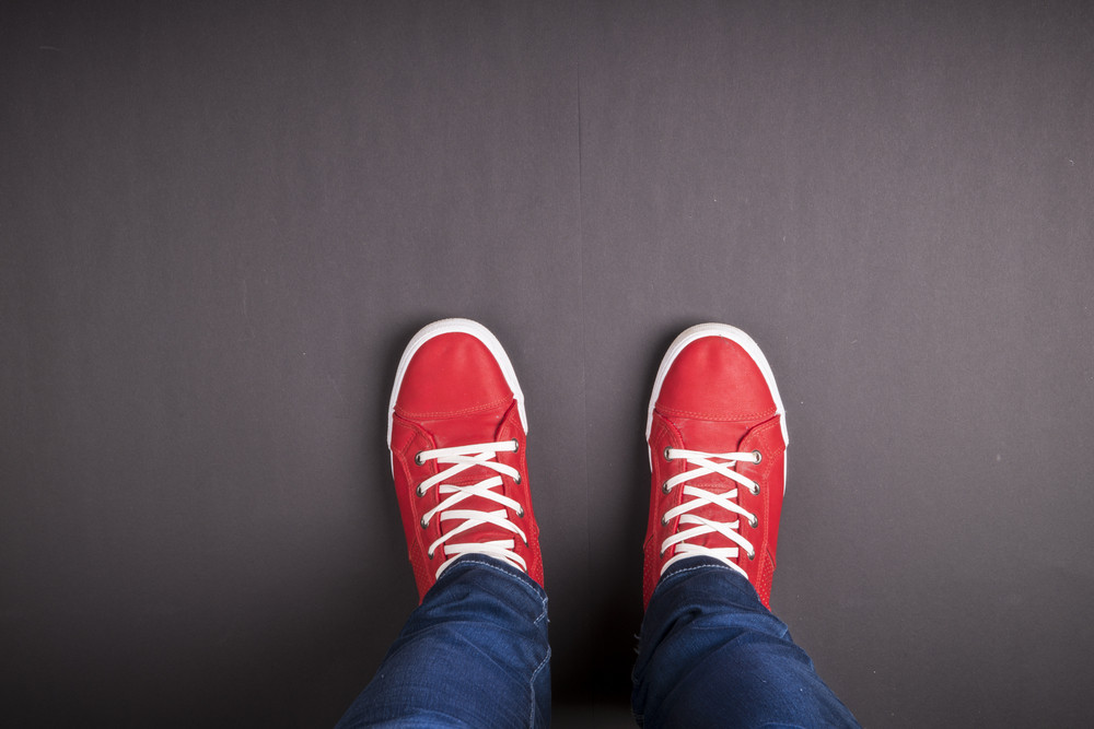 Feet concept - red shoes on black background with space for text or symbol