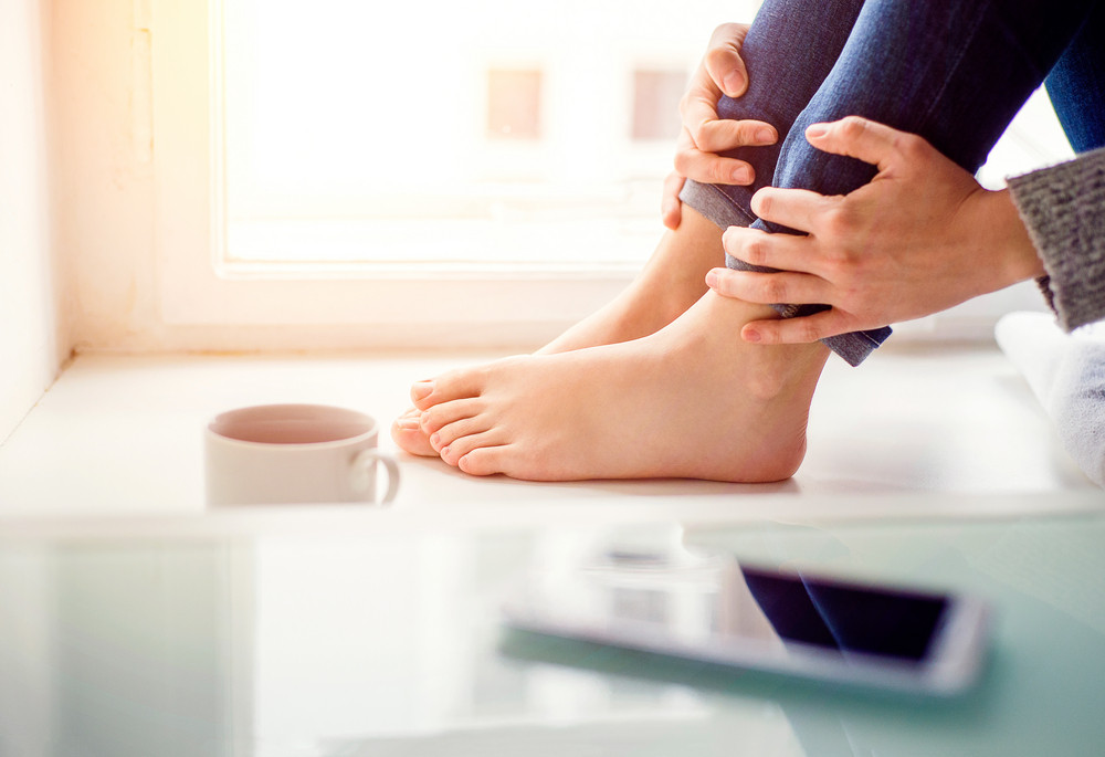 Feet of unrecognizable woman sitting on window sill with smart phone and cup of coffee