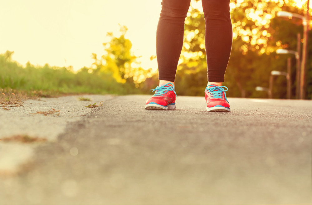 Female athlete in running shoes ready for a run on a forest path at sunset