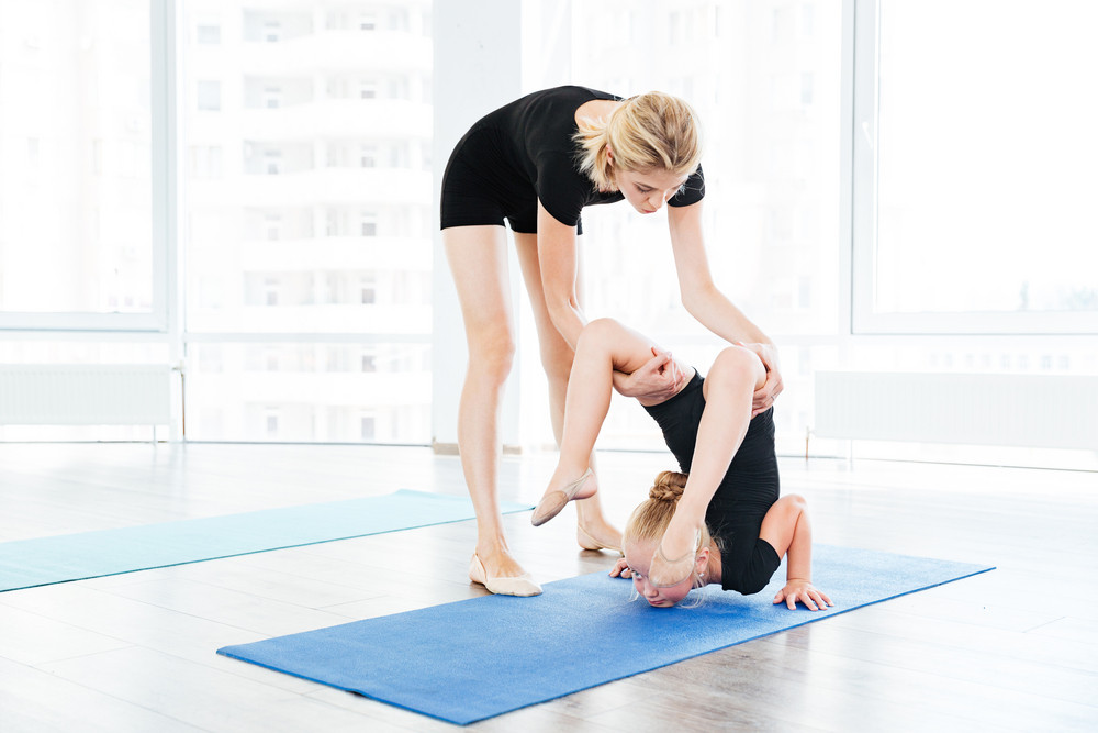 Female dance teacher doing stretching exercises with little gymnast girl at studio