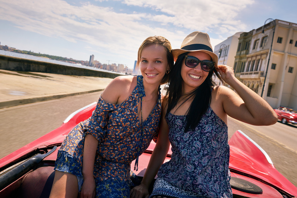 Female friends on holidays, people traveling, young women having fun on vacation, two happy girls smiling in Havana, Cuba. Hispanic persons laughing on old classic convertible car. Slow motion