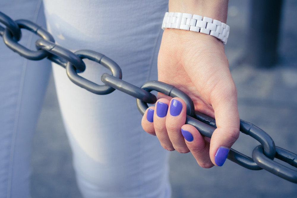 Female hand with blue manicure holding a metal chain outdoors