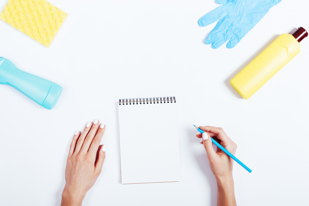Female hand writing in a notebook, yellow and blue bottle of detergent and a sponge on a white table top view