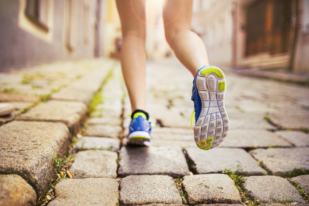 Female runner running on tiled pavement in city center, closeup on shoes