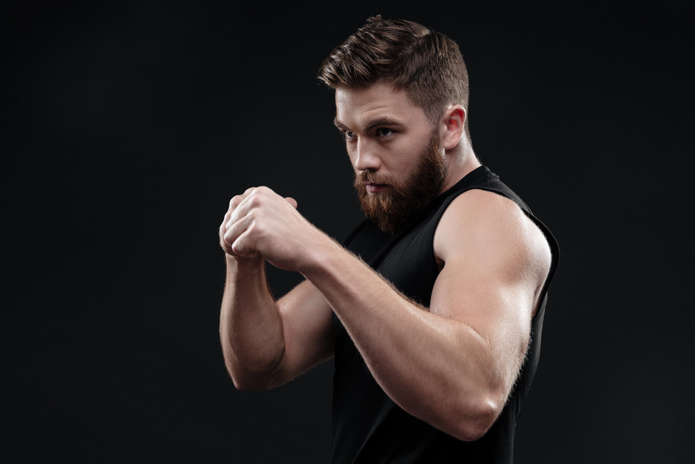 Fighter in studio. side view. isolated dark background