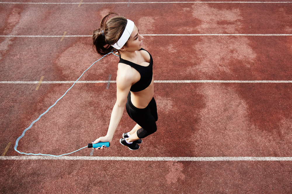 Fit girl exercising with skipping-rope at stadium