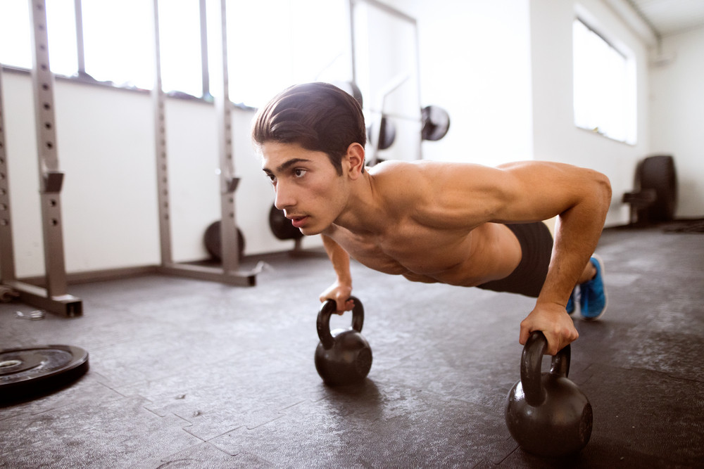 Fit hispanic man doing strength training, doing push ups on kettlebells in crossfit gym