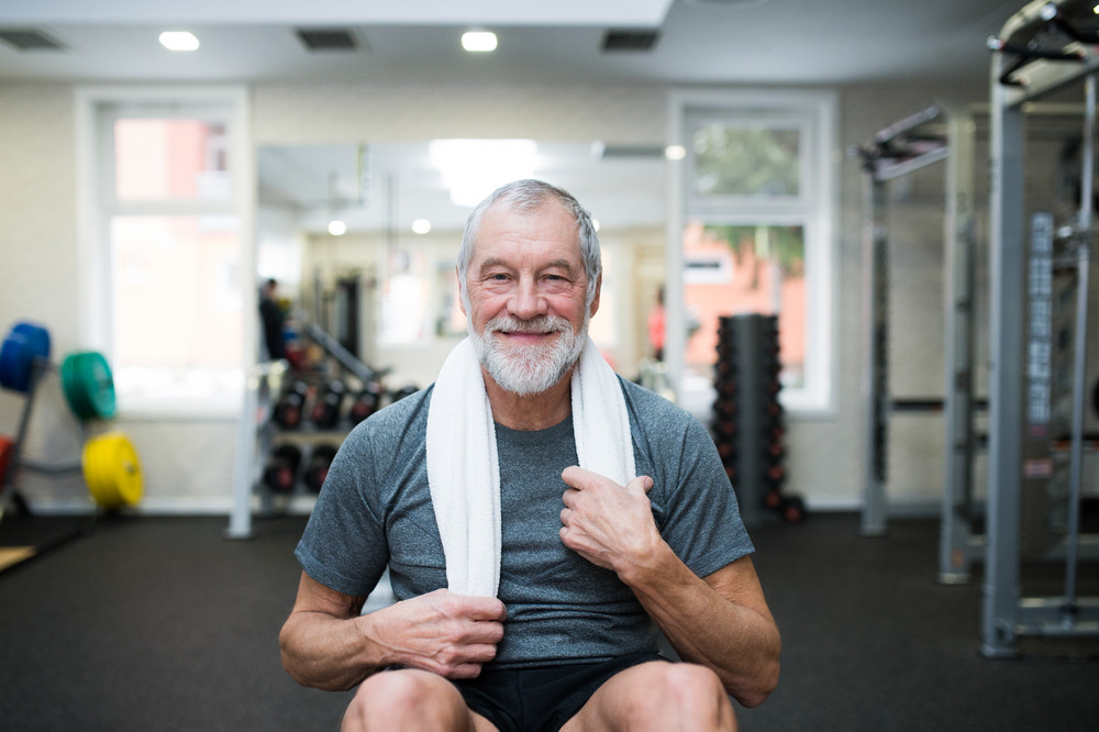 Fit senior man in sports clothing in gym resting after working out, towel around his neck