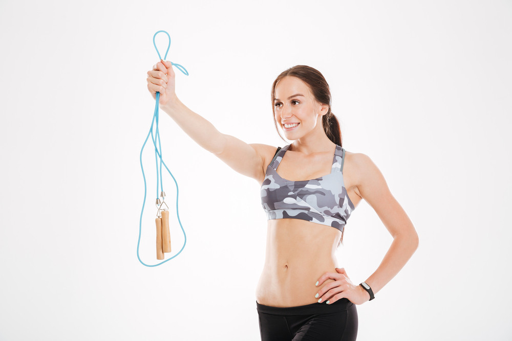 Fitness girl with skipping rope. looking away. isolated white background