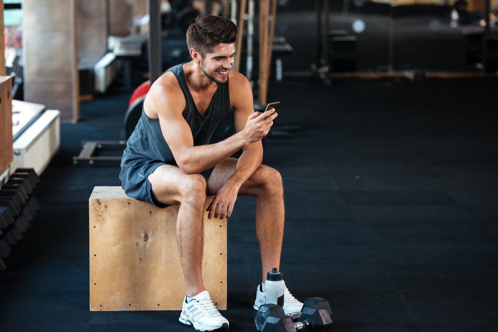 Fitness man sits on the box with phone. smiling