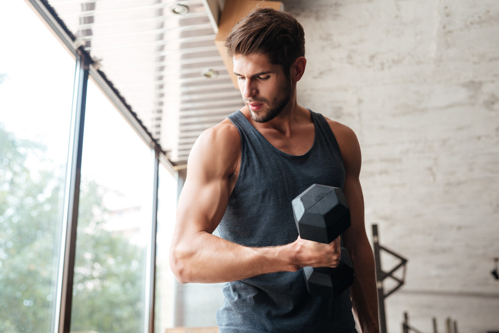 Fitness man with dumbbell in gym. looking away