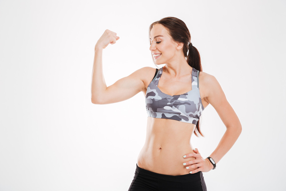 Fitness woman showing bicep in studio. isolated white background