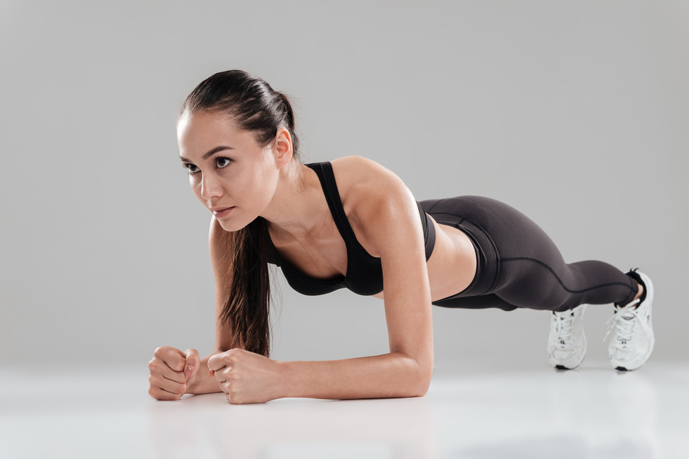 Focused beautiful young sportswoman working out and doing plank over gray background