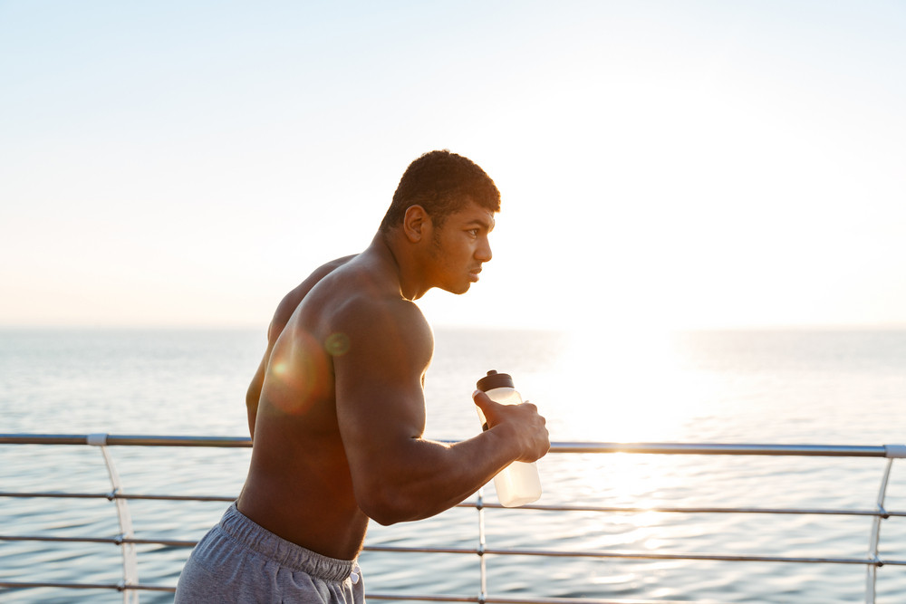 Focused shirtless african american young sportsman with bottle of water running on pier