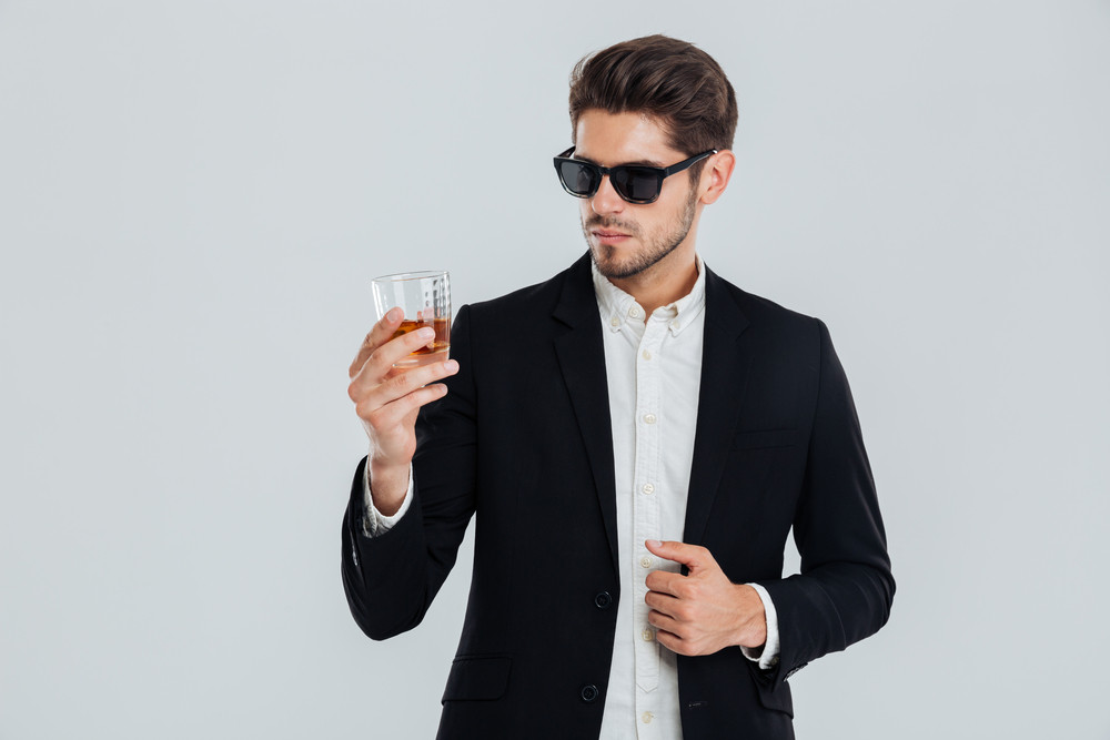 Focused young businessman in suite and sunglasses looking at whiskey in glass over gray background