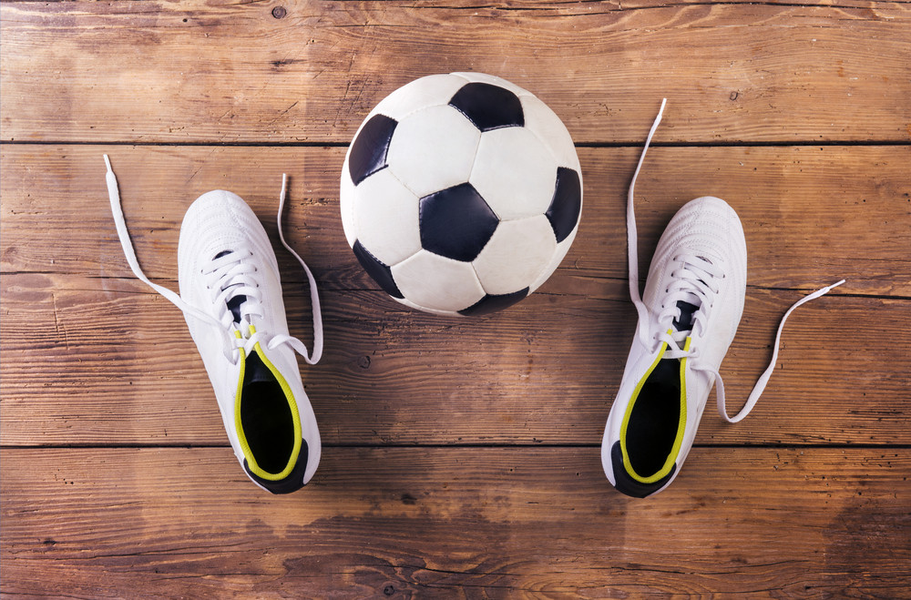97313fadd Football boots and ball laid on a wooden floor background Royalty ...