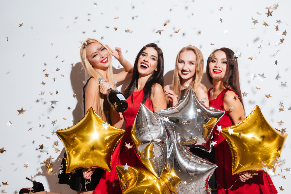 Four cheerful women with star shaped balloons and confetti drinking champagne and having party over white background