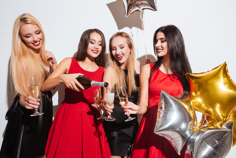 Four happy beautiful young women drinking champagne on the party over white background
