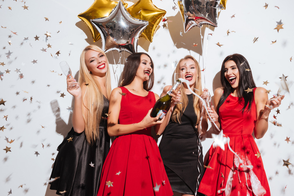 Four happy young women celebrating and opening bottle of champagne on the party over white background