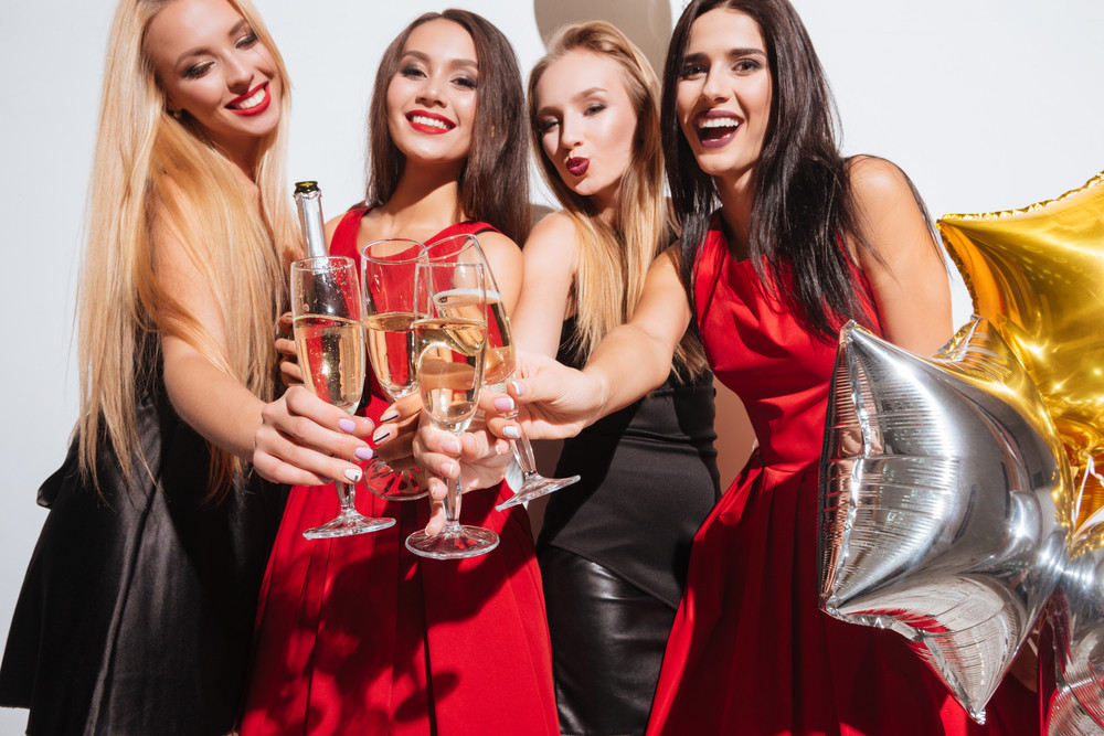 Four joyful attractive young women clinking glasses and drinking champagne on the party over white background