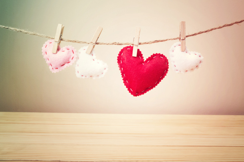 Four Small White, Pink and Red Hearts with Stitches Hanging on a String with Clothespin above the Wooden Table on Light Brown Background