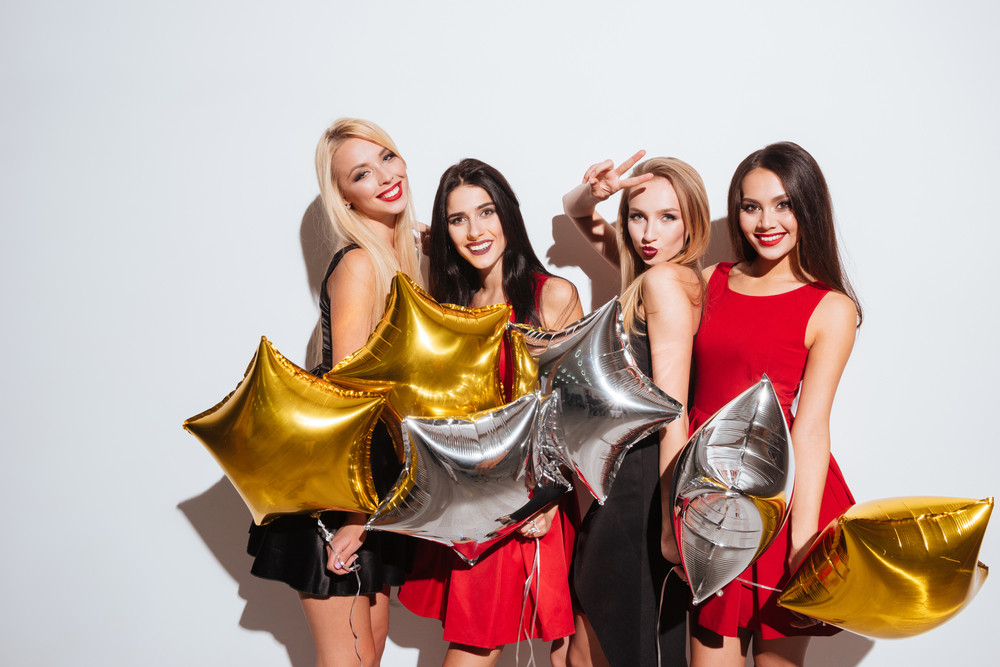 Four smiling attractive girls standing and holding star shaped balloons over white background