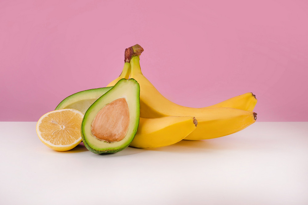 Fresh bananas, sliced avocado and lemon on table isolated on pink background
