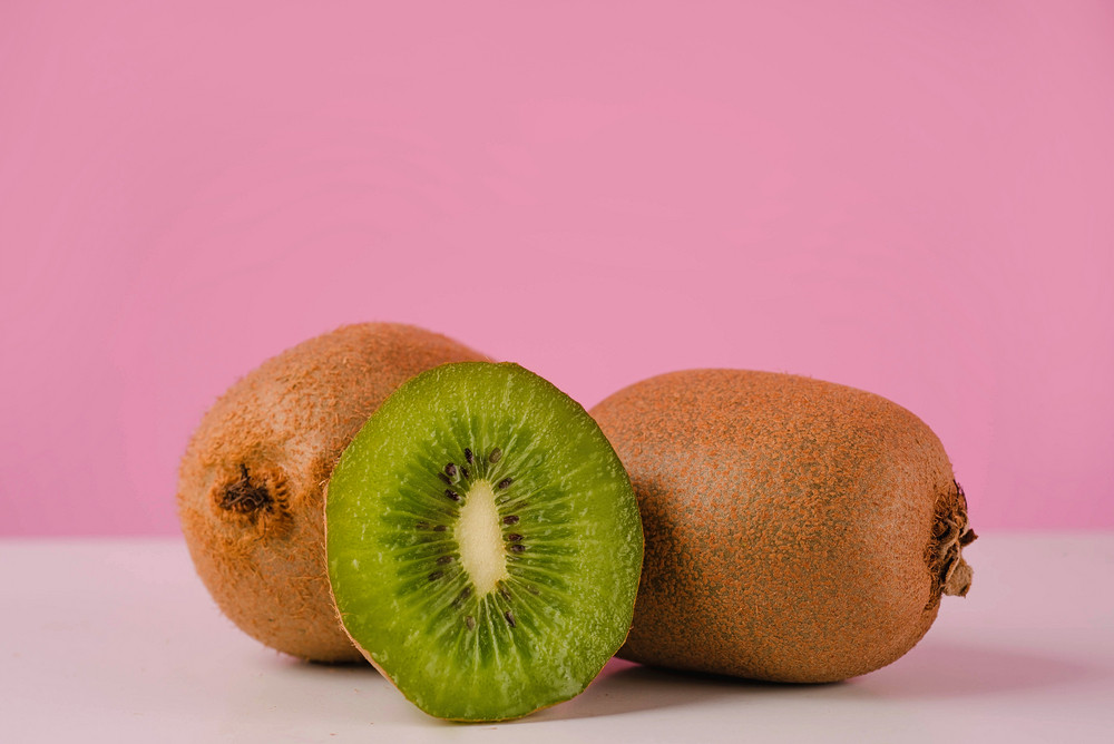 Fresh juicy sliced kiwi fruit on a table isolated on pink background