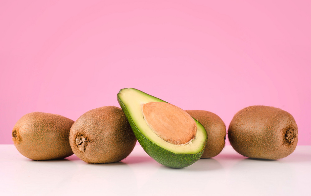 Fresh kiwi and sliced avocado on a table isolated on pink background