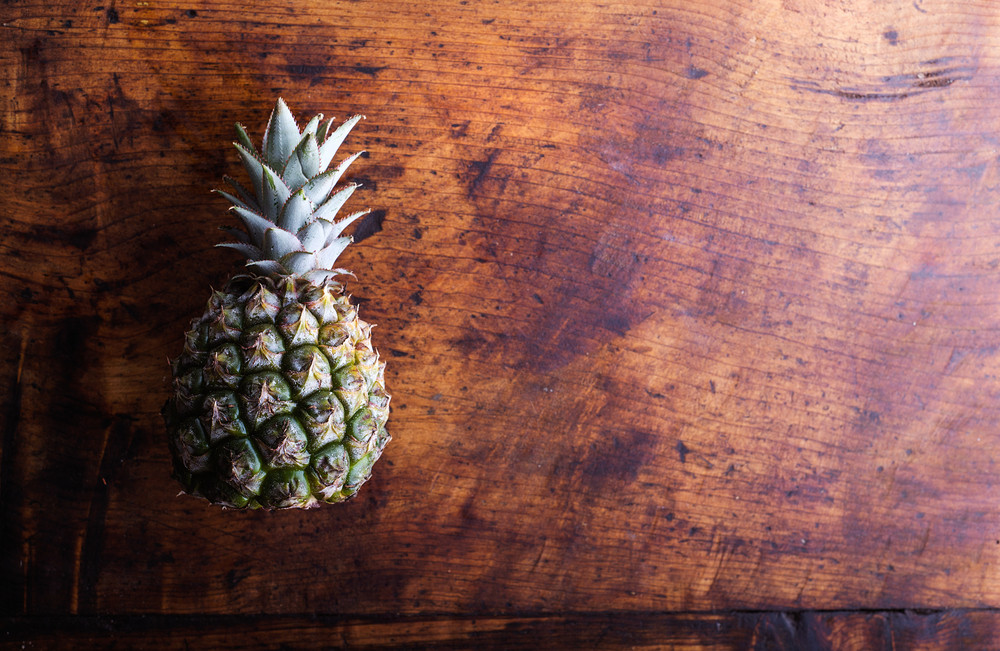 Fresh ripe pineapple laid on a table. Studio shot on wooden background.
