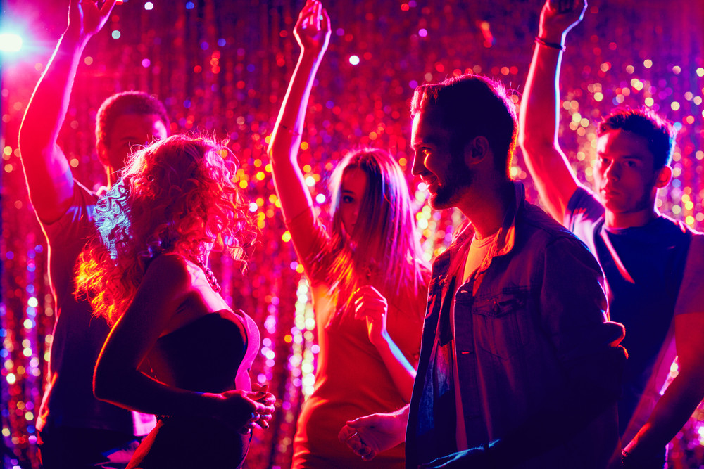 Friendly clubbers dancing at party