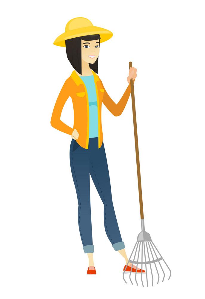 Friendly female asian farmer standing with gardening rake. Full length of young smiling farmer in summer hat holding a gardening rake. Vector flat design illustration isolated on white background.