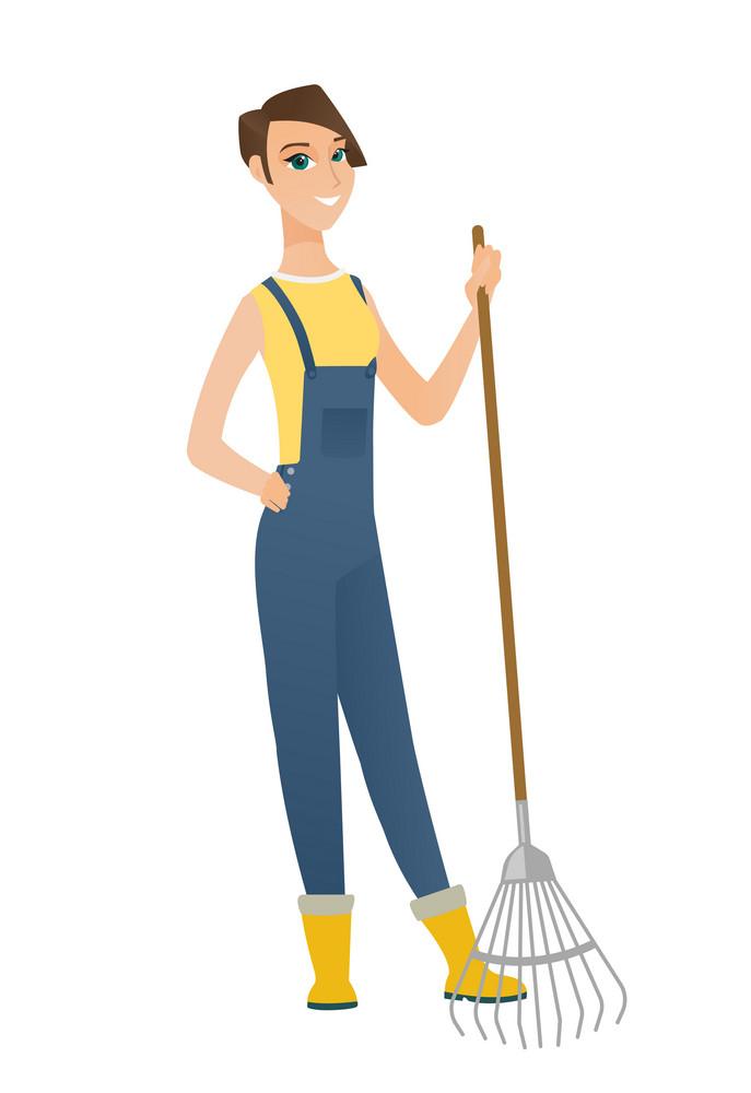 Friendly female caucasian farmer standing with gardening rake. Full length of young smiling farmer in overalls holding a gardening rake. Vector flat design illustration isolated on white background.