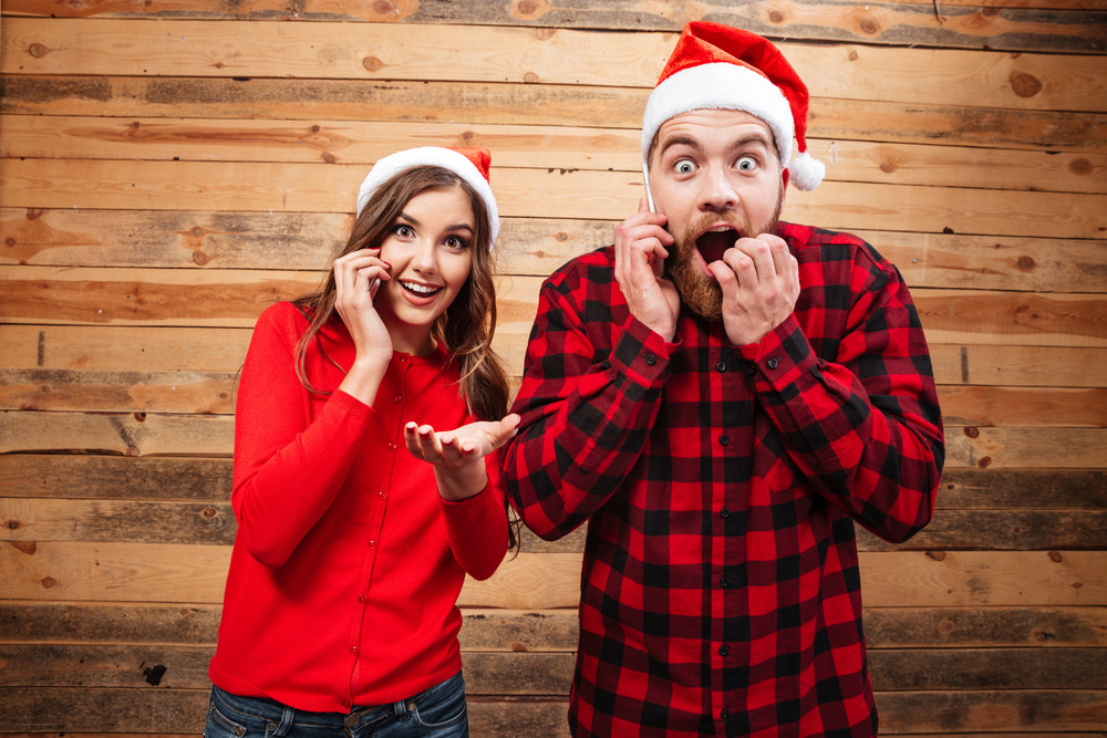 Friends in santa's hats looking at camera. shocked. wooden background