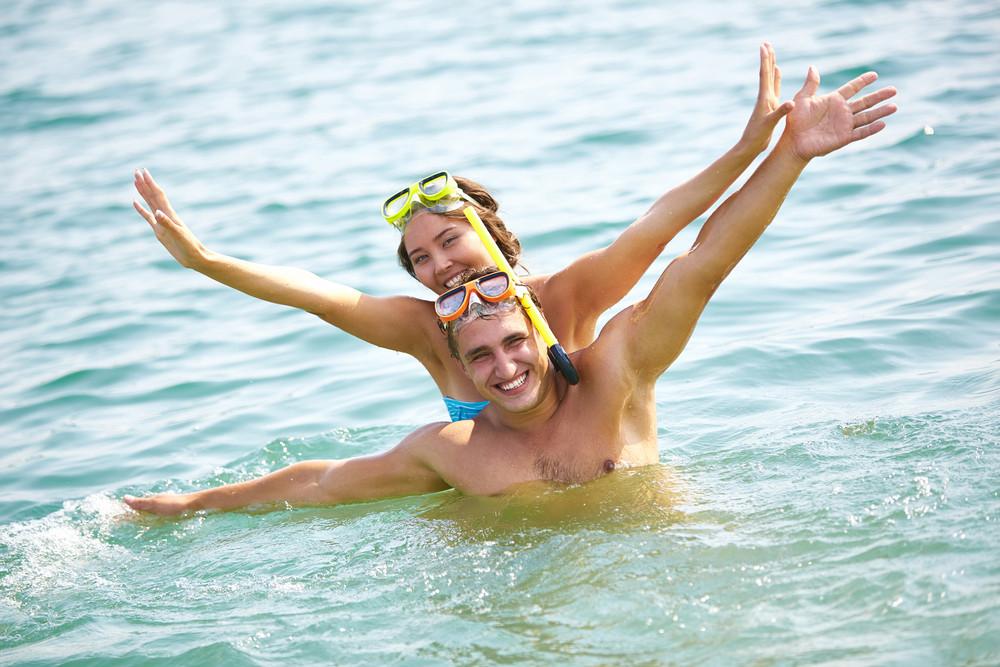Friends in scuba masks having fun in summer water