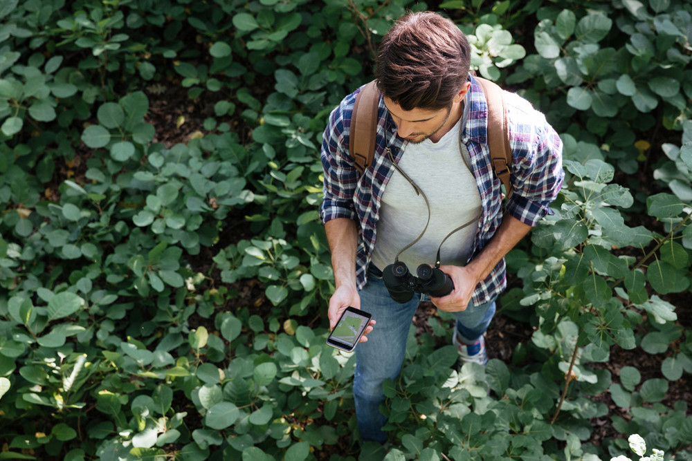 From above image of guy in forest in the midst of plants. with binoculars and phone.