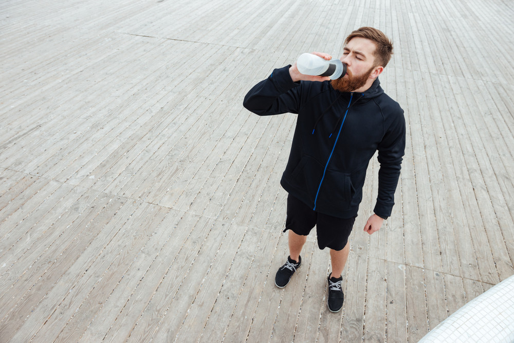 From above portrait of runner. full length image. drink water
