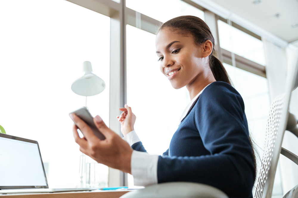 From below image of smiling afro business woman in dress looking at phone in office