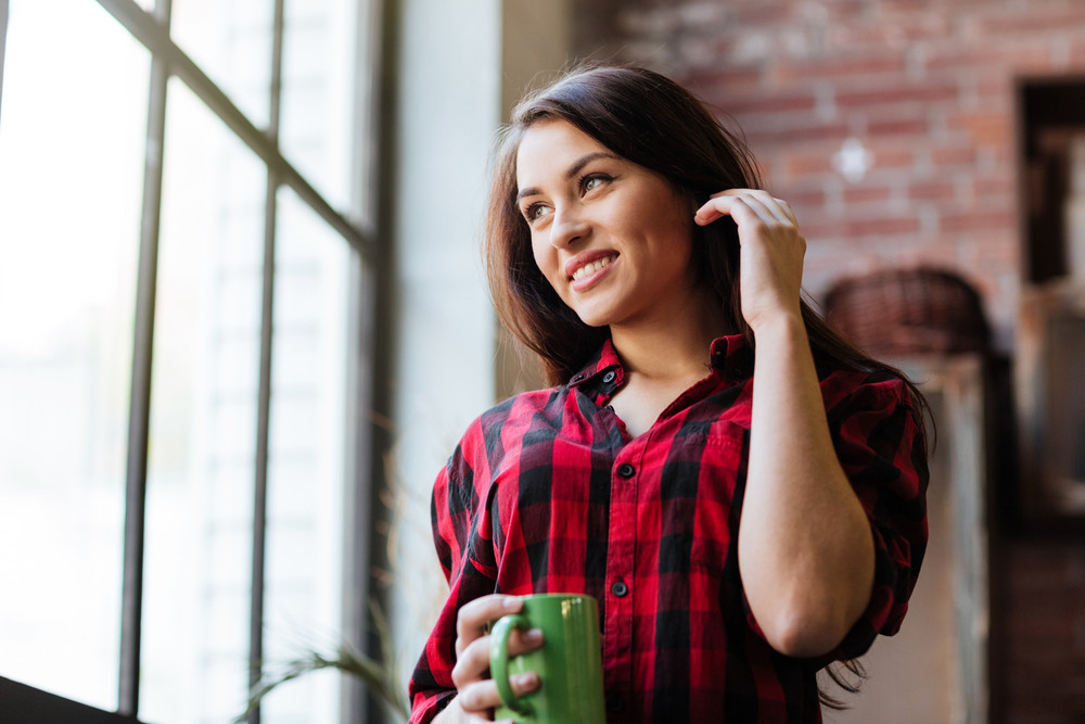 From below image of smiling Woman in red shirt with cup of tie near the window looking away