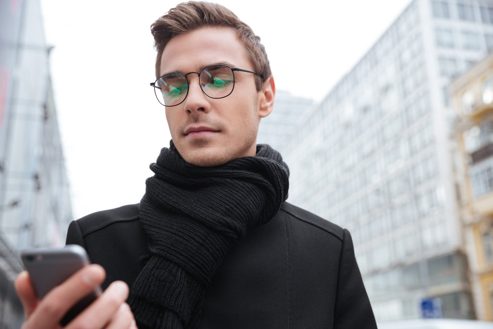 From below image of young business man in glasses with phone on the street